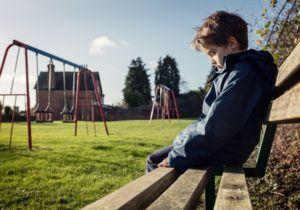 Mutismus Beratung Psychopharmaka depressiver Junge mit gesenktem Blick sitzt auf einer Parkbank