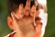 Kind das die Hand vor die Kamera hält